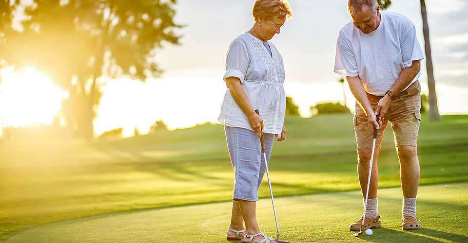 Senior couple playing golf at sunset